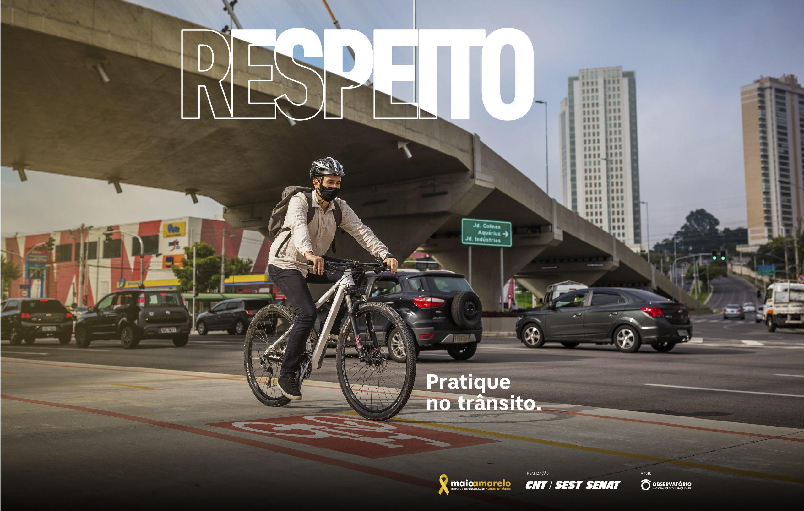 ciclista de capacete pedala em ciclovia com transito em segundo plano