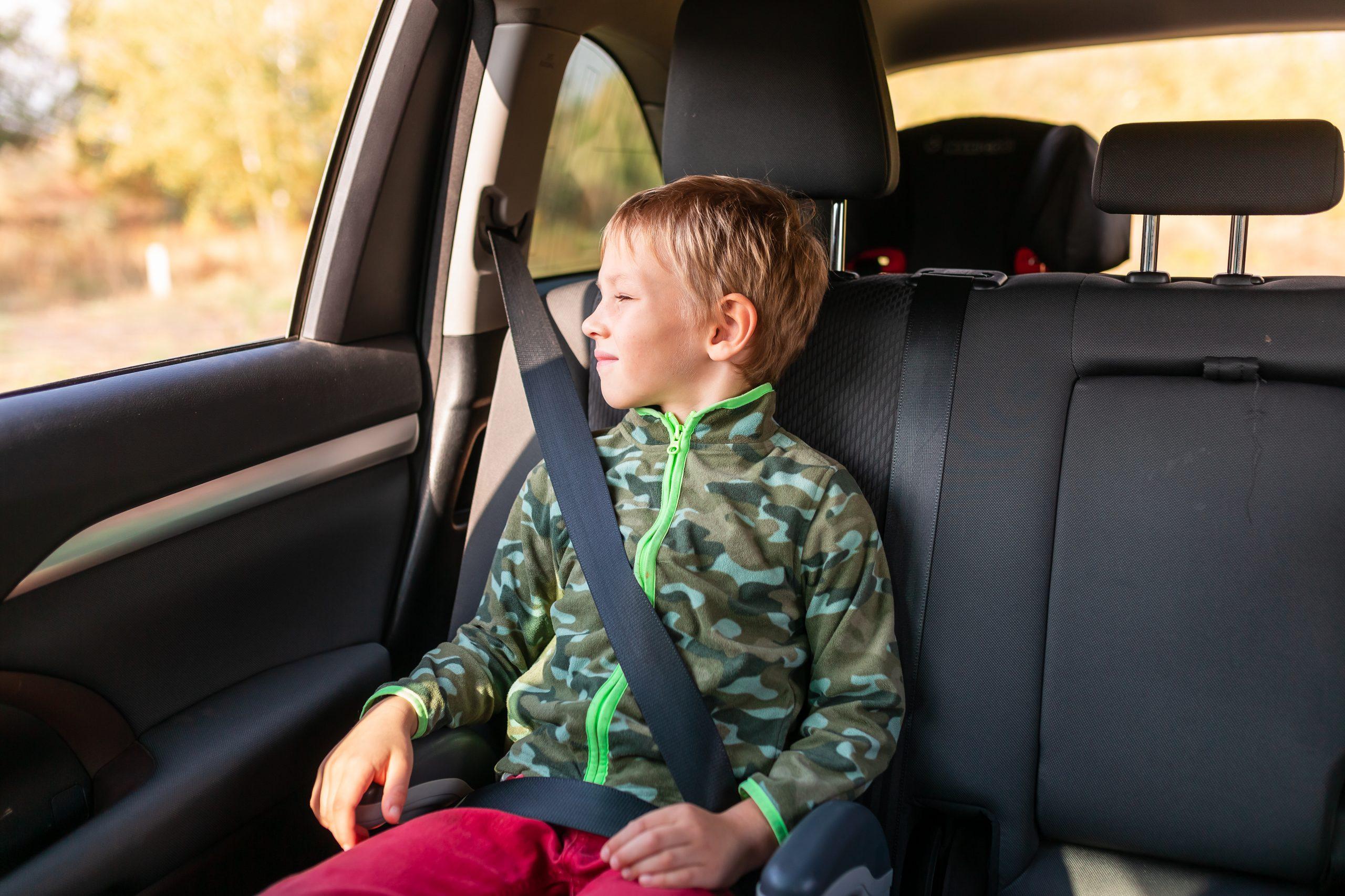 menino com blusa de frio sentado no banco traseiro do carro com booster