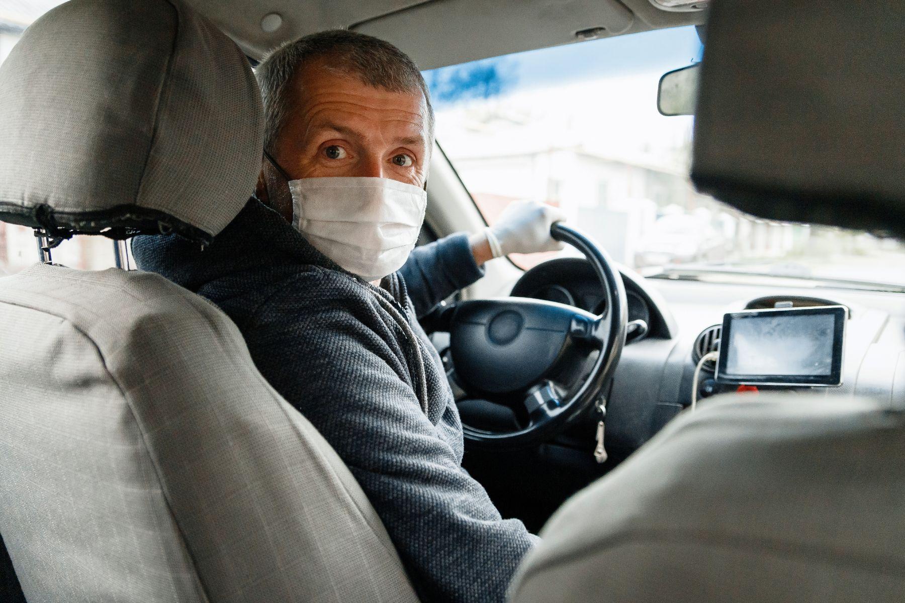 motorista profissional de mascara olhando para o banco de tras