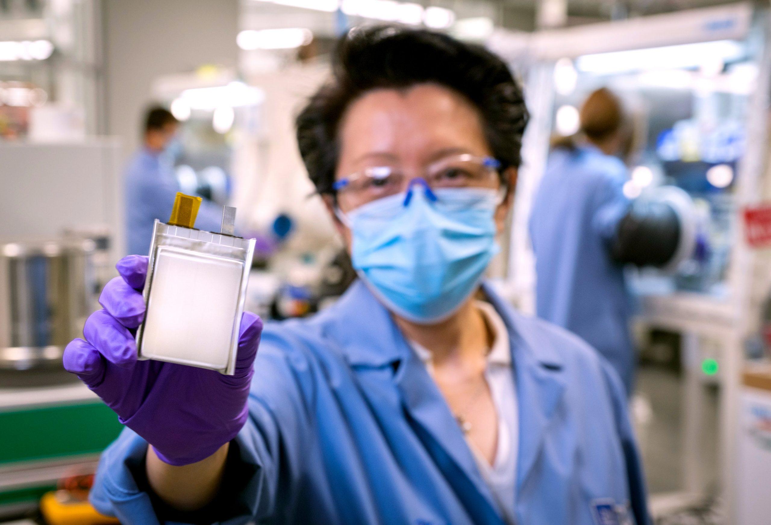funcionario da general motors gm de mascara e uniforme azul mostra bateria ultium desenvolvida pela empra nos eua