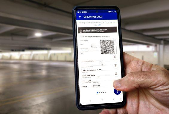mao masculina segurando celular com o documento do carro digital ou crlv-e aberto em estacionamento fechado