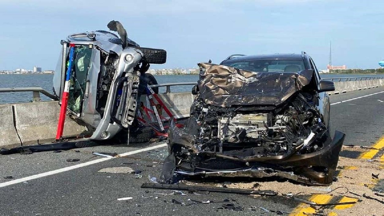 dois carros destruidos em acidente de trânsito sobre uma ponte