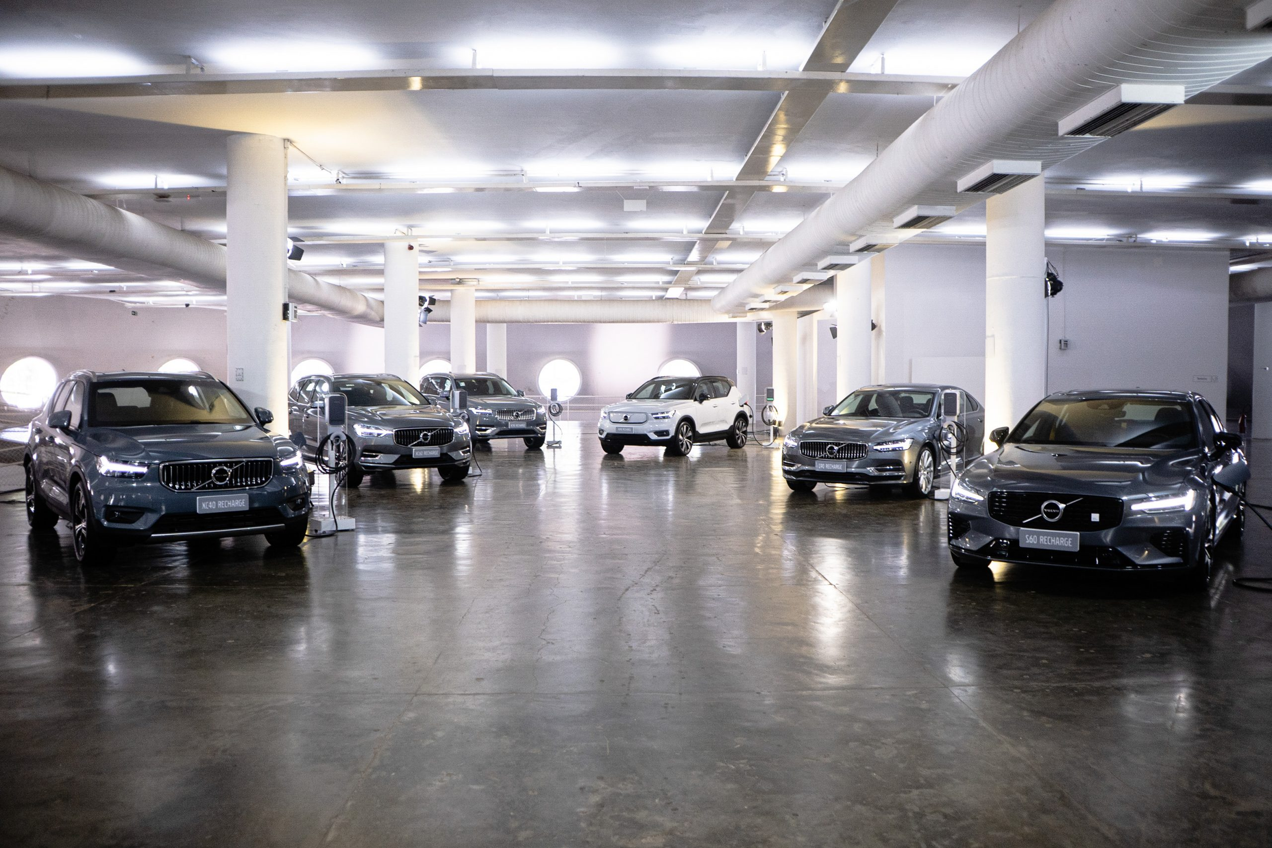 frota de carros eletricos da volvo carregando em estacionamento coberto