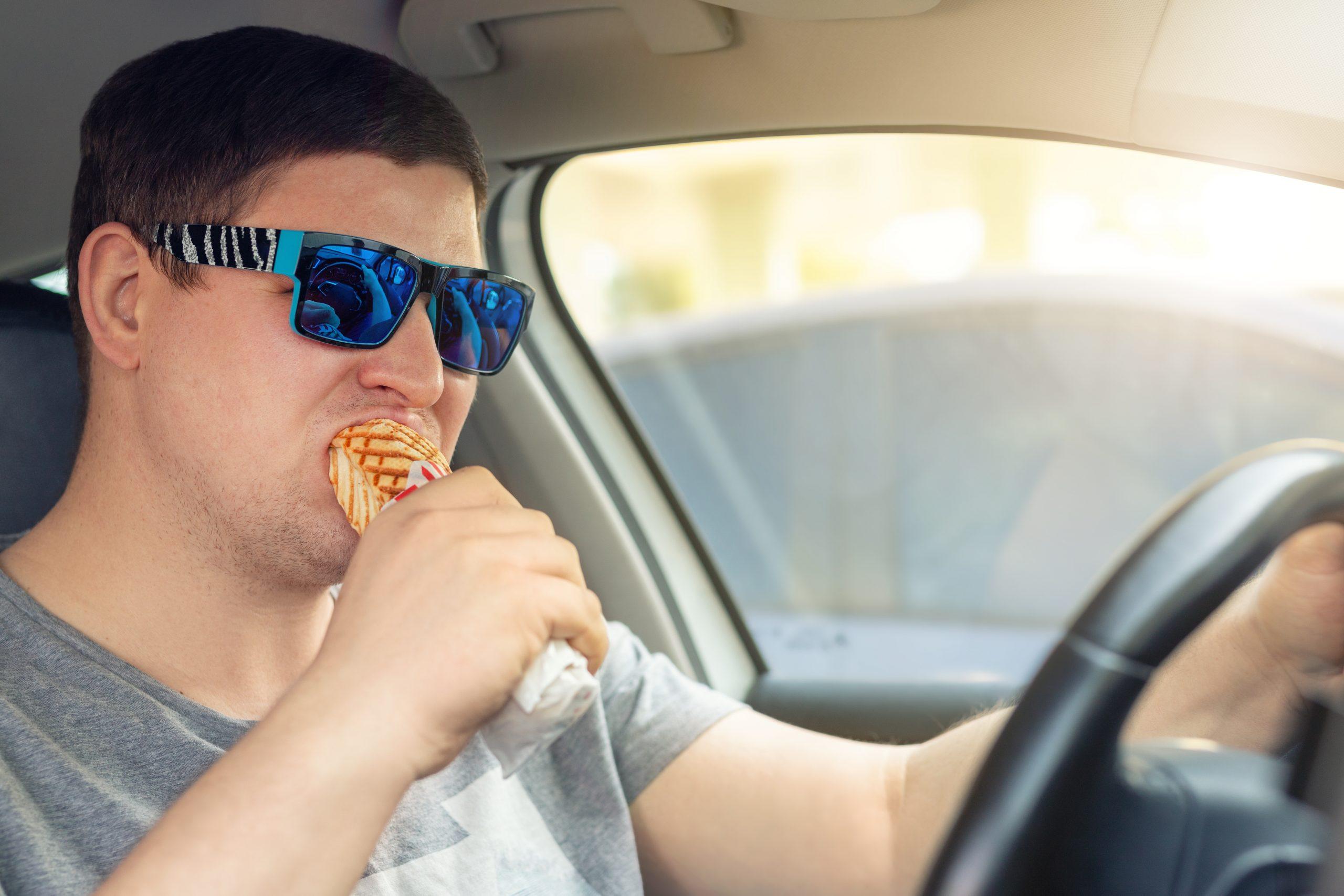 motorista comendo salgado enquanto dirige mantando apenas uma mao no volante do carro