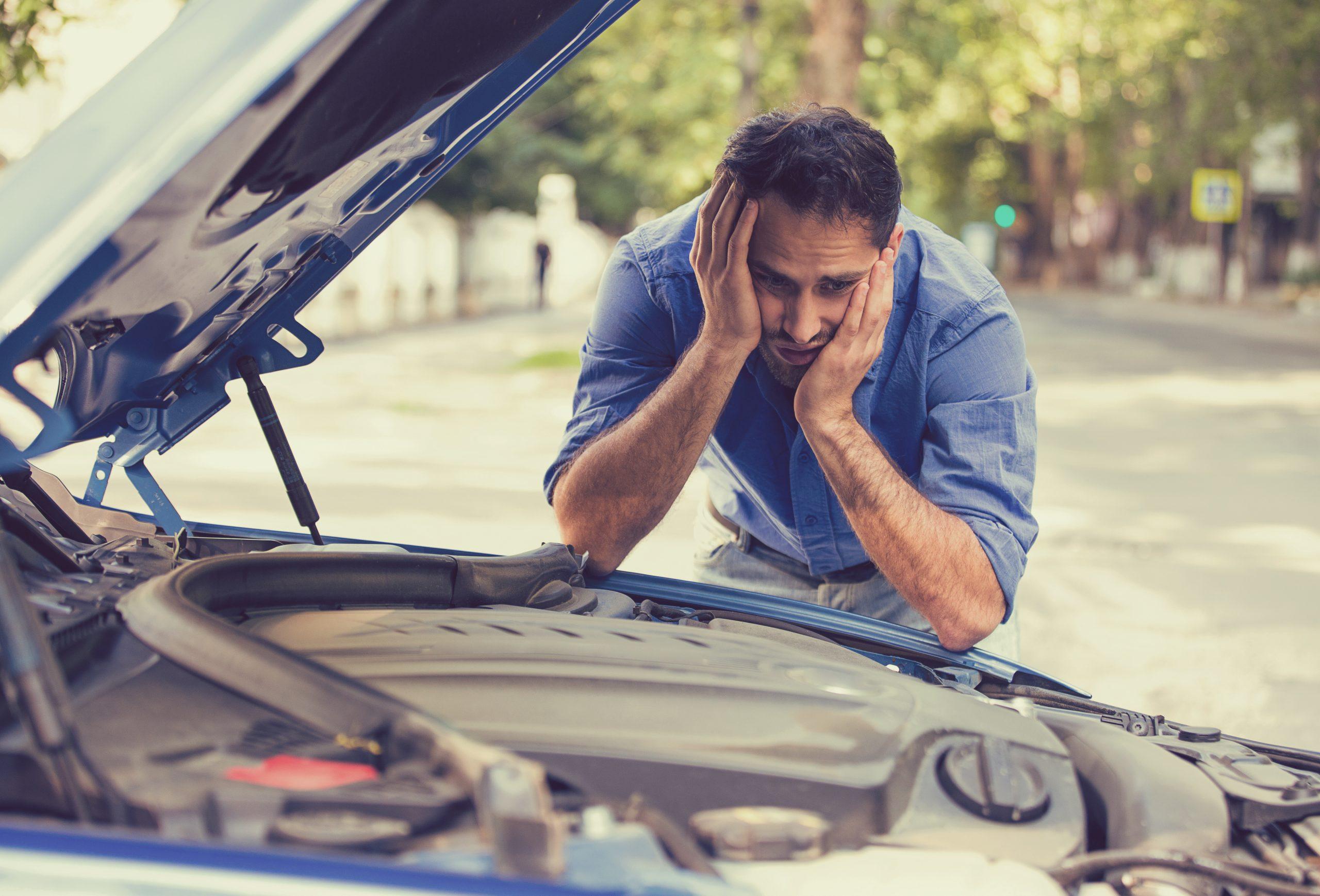 motorista chateado com carro quebrado