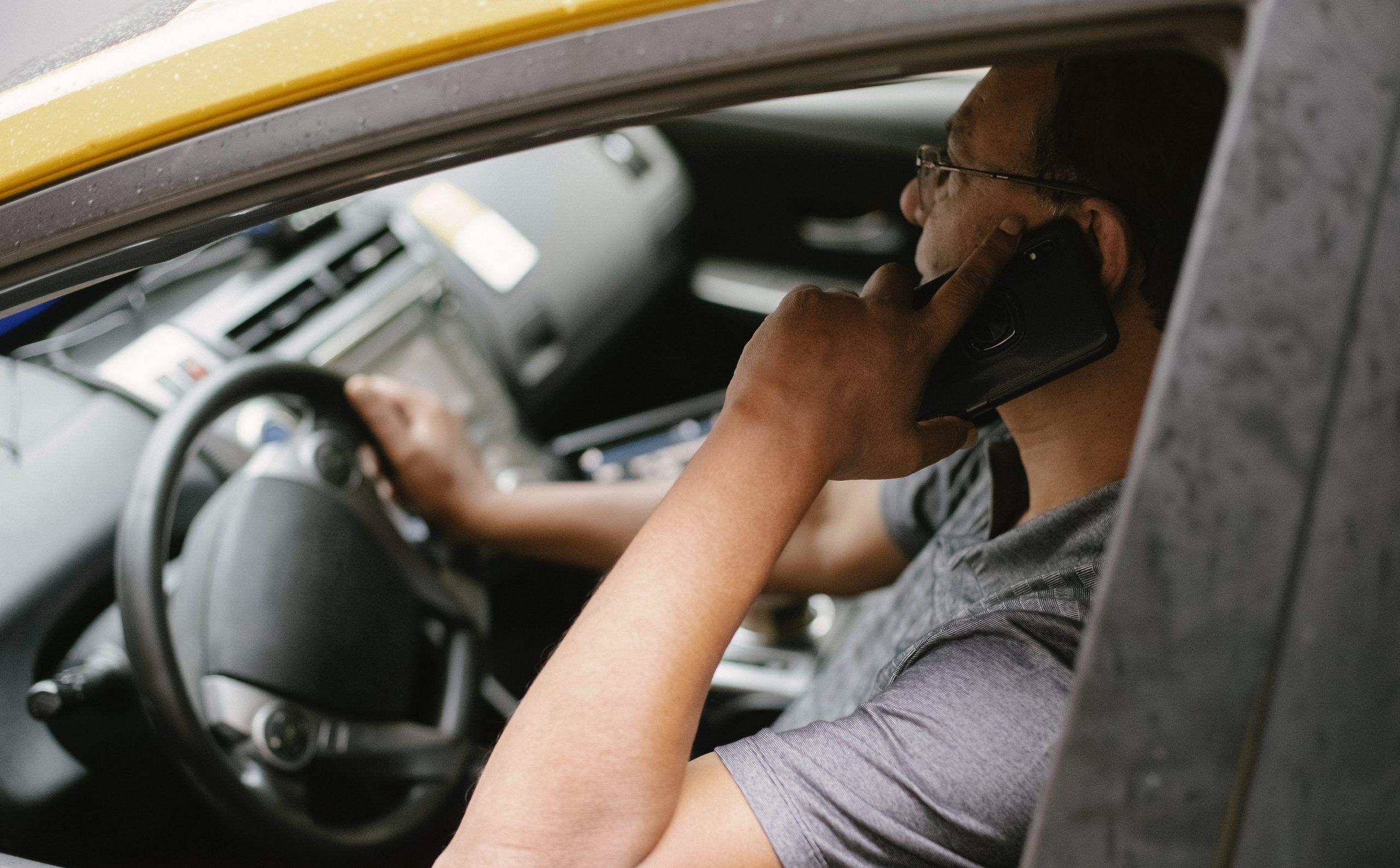 Motorista desatento no trânsito segurando volante com apenas uma mão