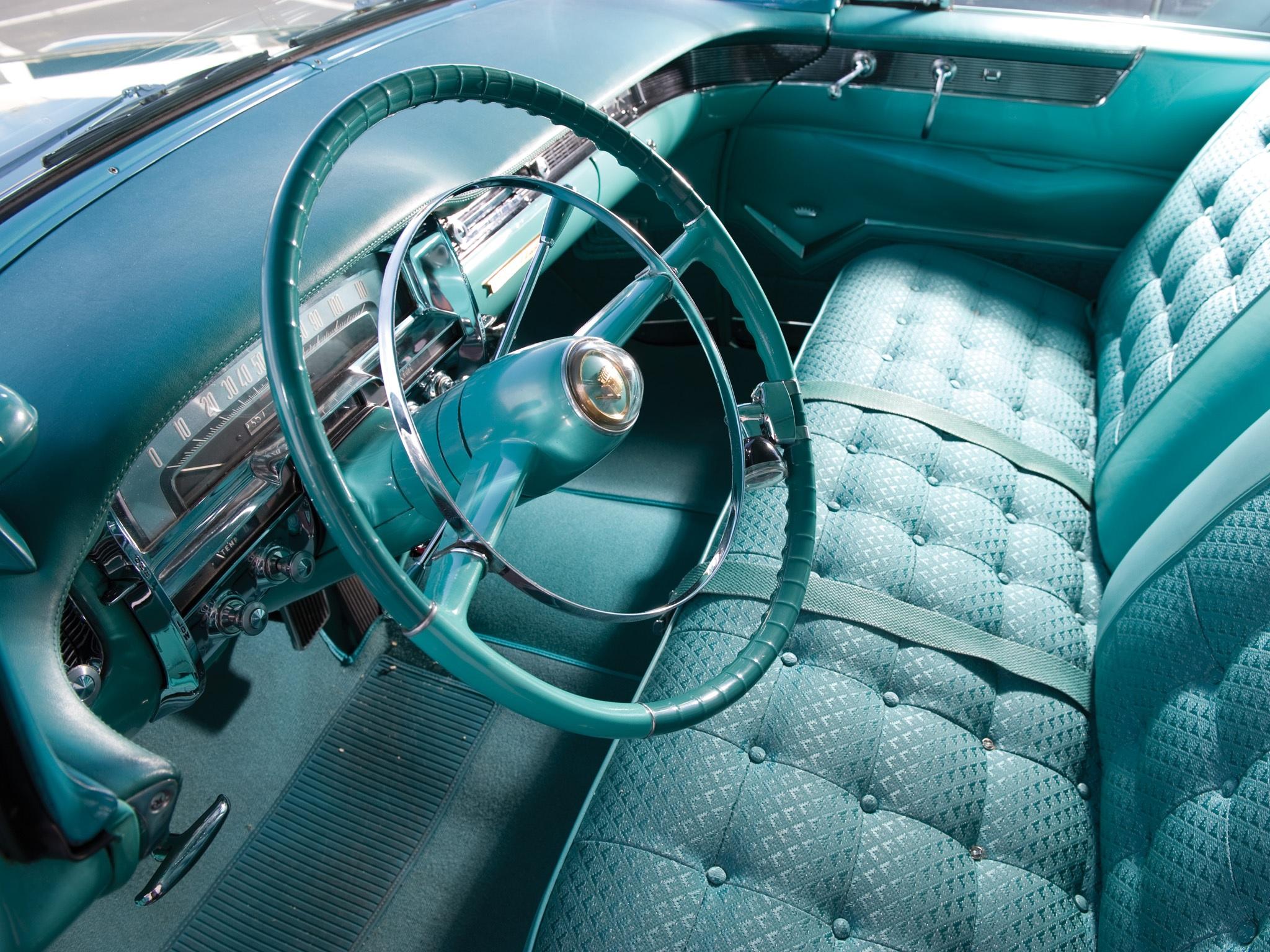 interior do cadillac de ville 1955 com destaque para o volante em forma de ogiva