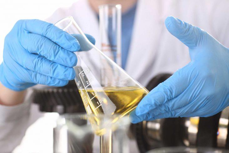 tecnico com luvas de borracha analisa gasolina dentro de erlenmeyer em laboratorio foto shutterstock