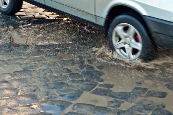 carro transita sobre calcamento irregular com pocas de agua e submete suspensao a esforcos foto shutterstock