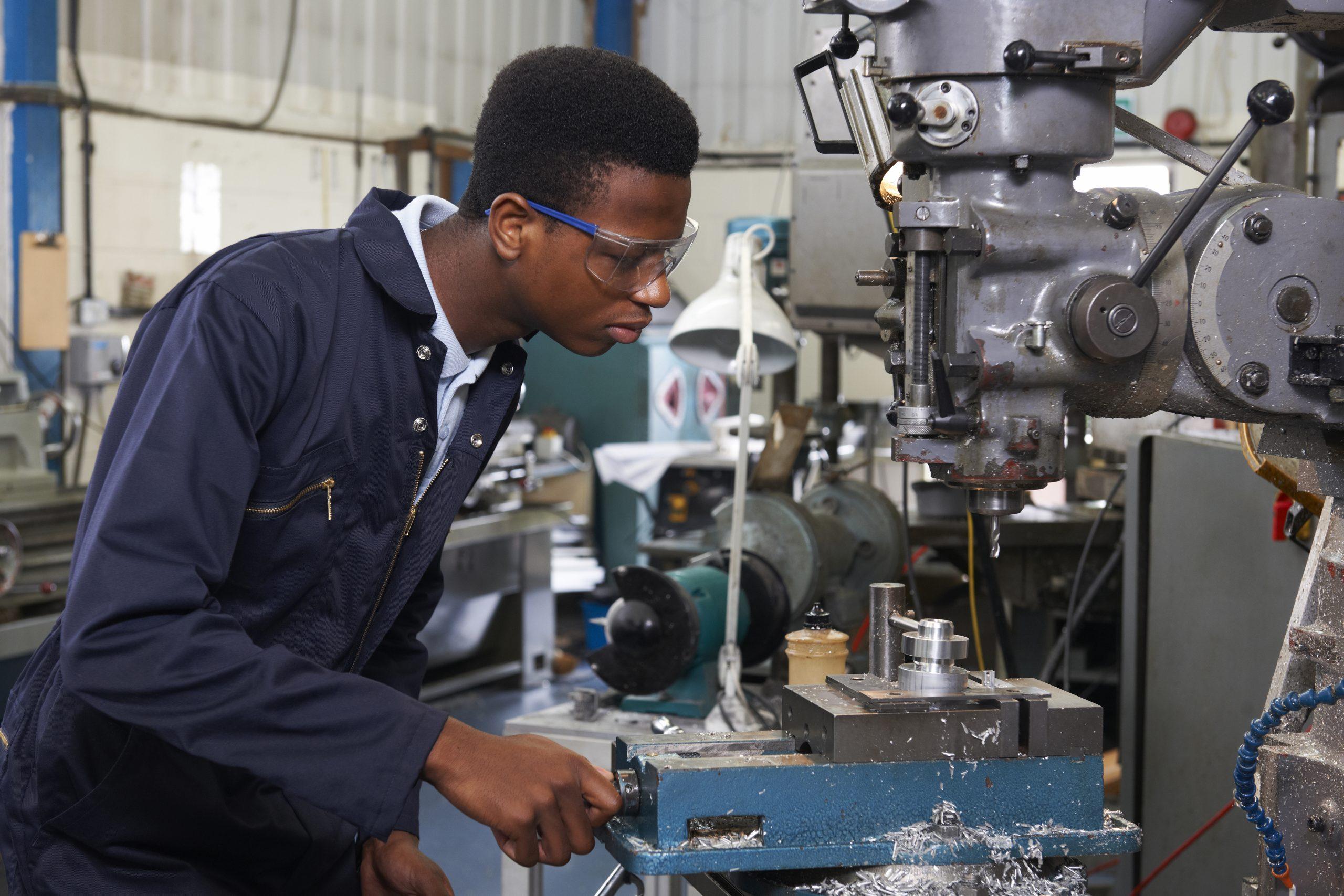 jovem aprendiz de engenharia operando maquina