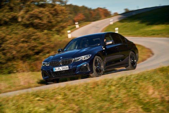 bmw m340i xdrive azul escuro frente em movimento fazendo curva em rodovia simples