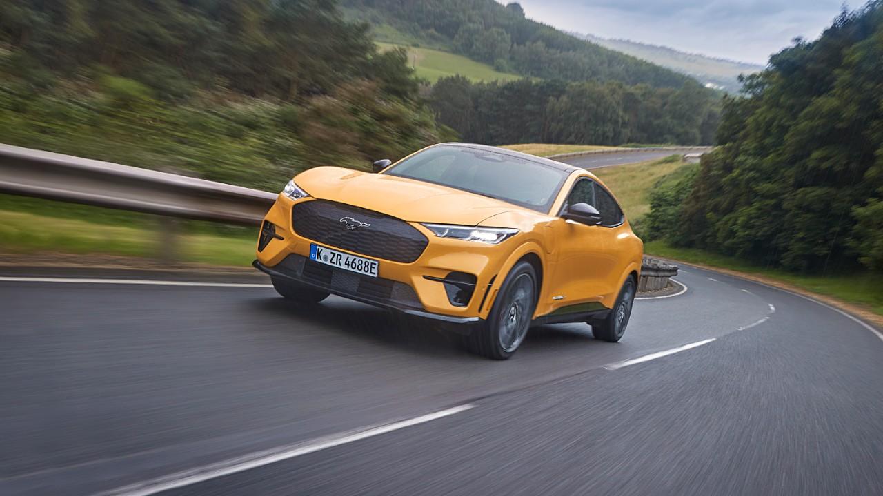 ford mustang mach e gt 2021 laranja modelo europeu em uma rodovia de pista simples