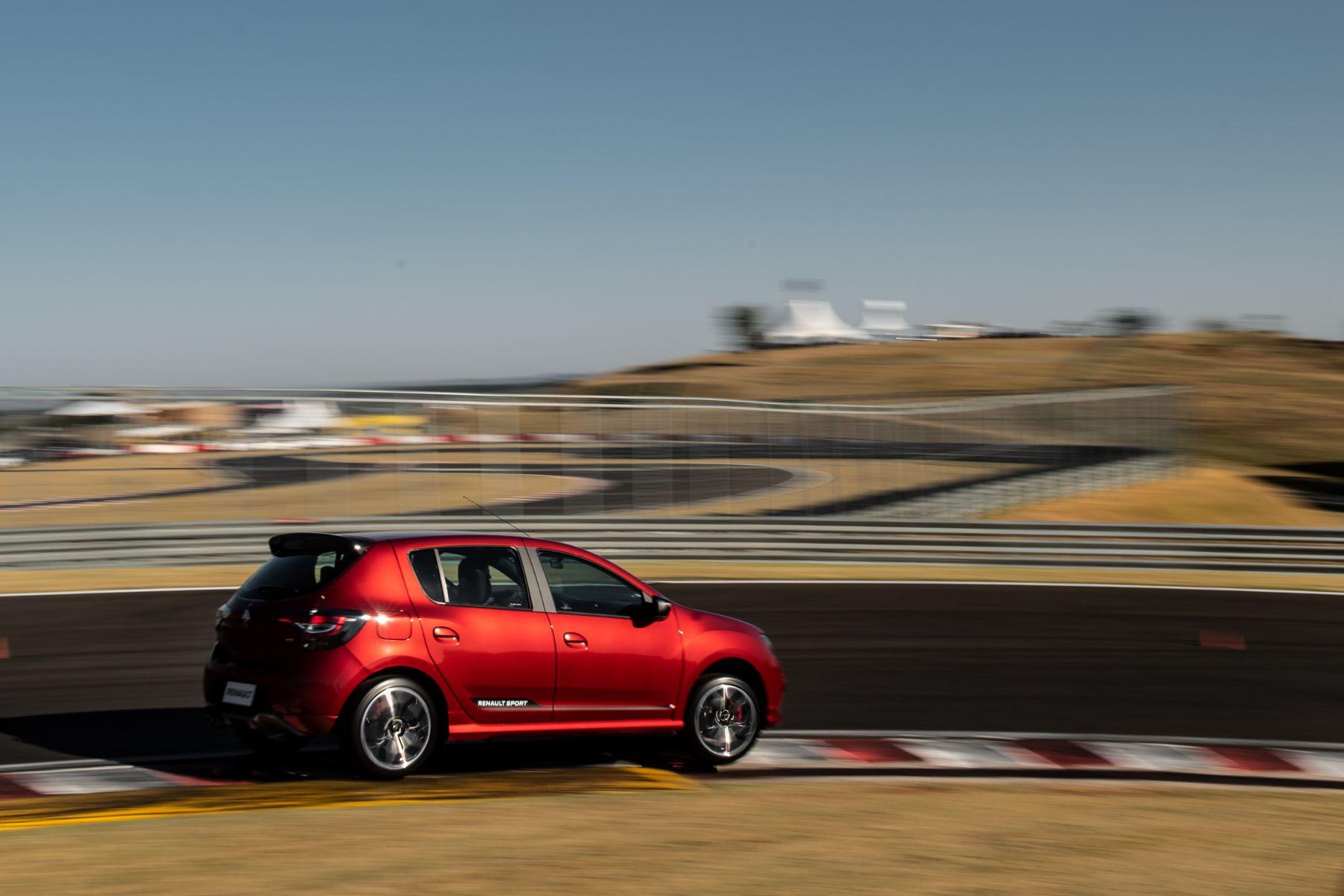 renault sandero r s vermelho lateral fazendo curva forte em autodromo