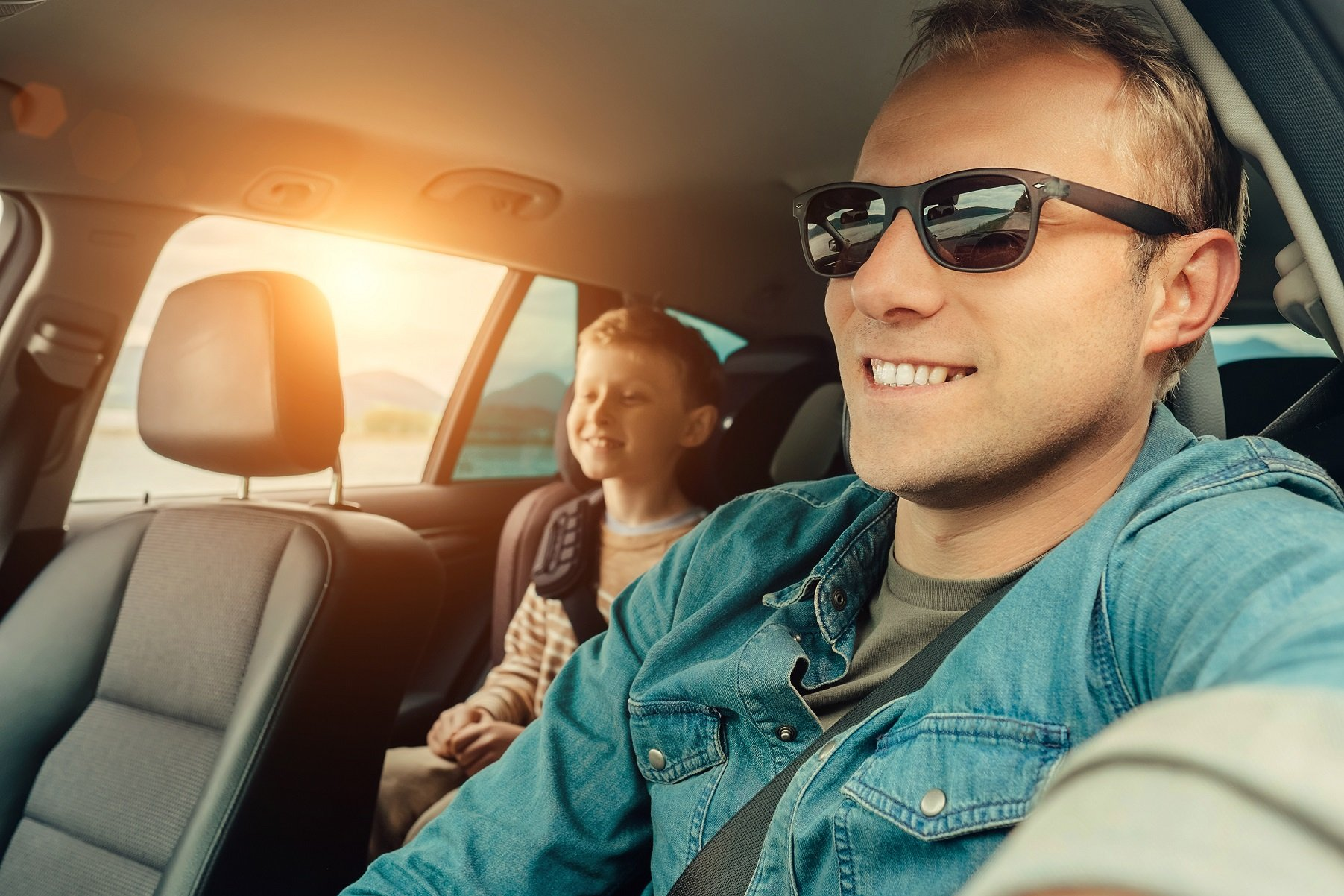 pai dirigindo carro com filho sentado em cadeirinha no banco traseiro