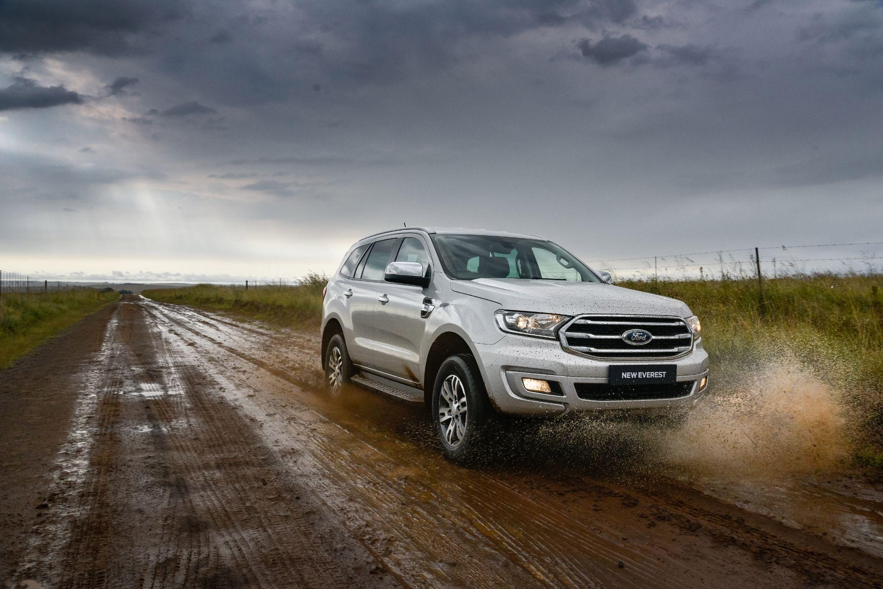 ford everest xlt prata frente em estrada de terra molhda