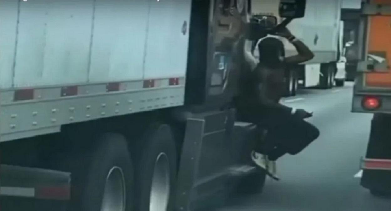homem flagrado pendurado em retrovisor de carreta